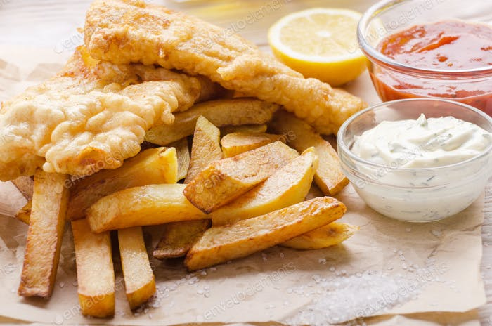 Traditional British street food fish and chips with ketchup and