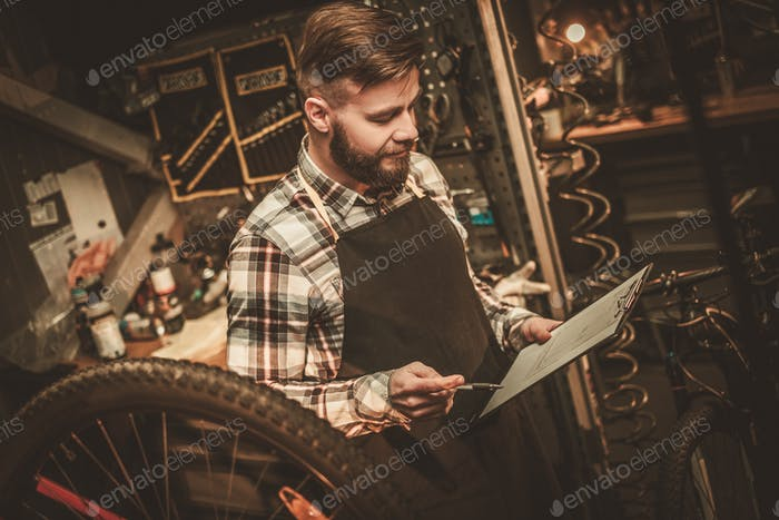 Stylish bicycle mechanic making notes in clipboard in his workshop.