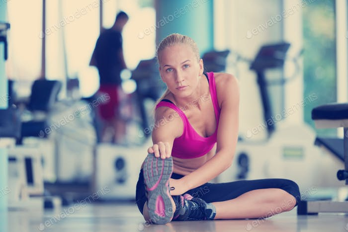 woman stretching and warming up for her training at a gym