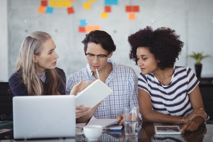 Confident business people using digital tablet in creative office