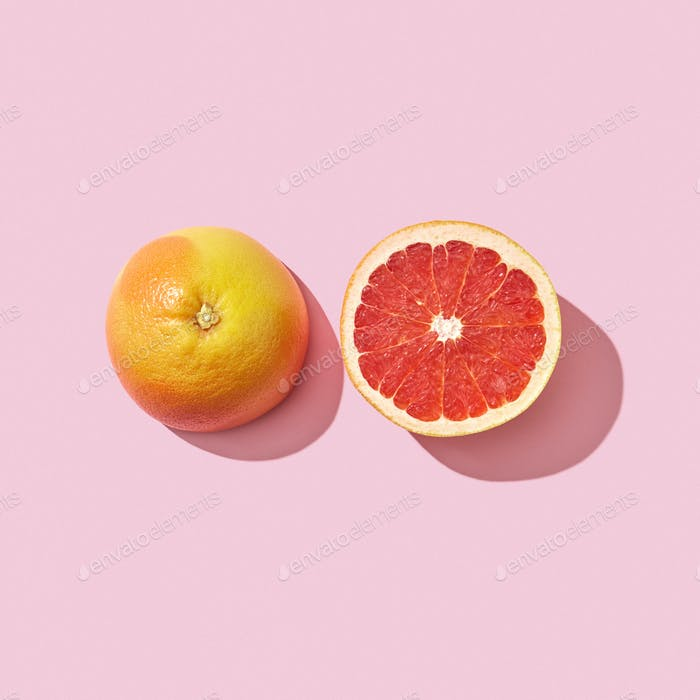 Two halves of a ripe grapefruit on a pink background with reflection of the shadow and space for