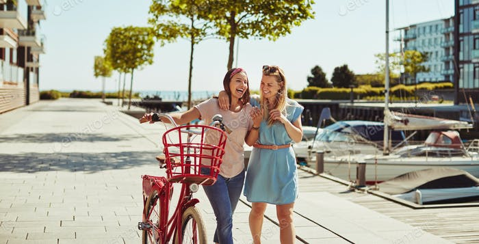 Laughing friends walking together with a bicycle through the city