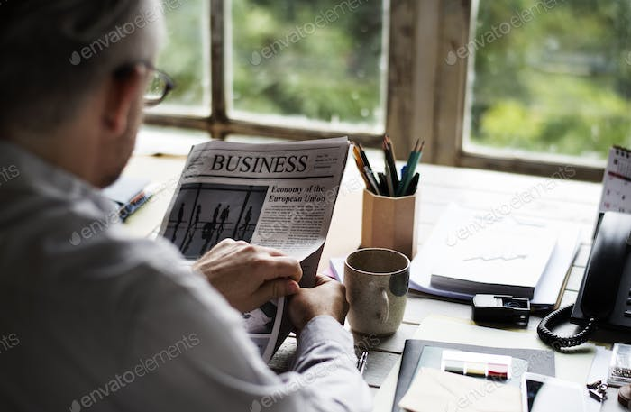 Businesspeople Reading Newspaper at Office Updating News