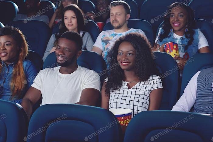 Friends watching movie in modern cinema hall