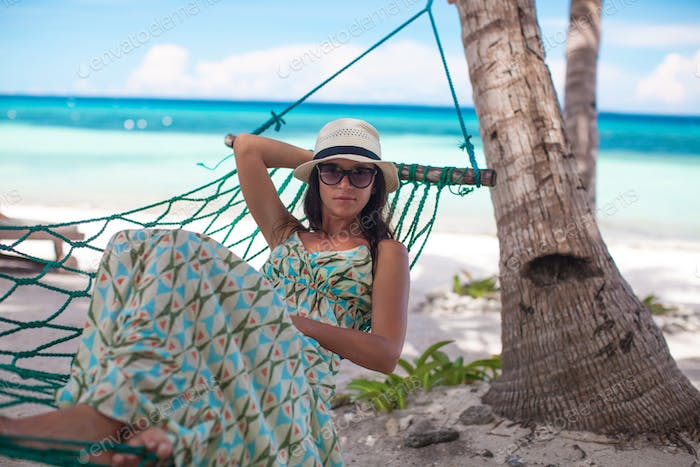 Happy young woman relaxing in the hammock on sunny day