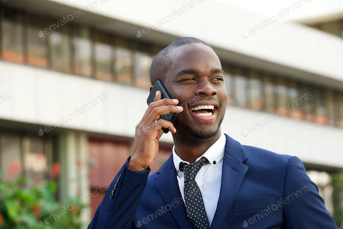 Close up black corporate businessman talking with mobile phone in the city