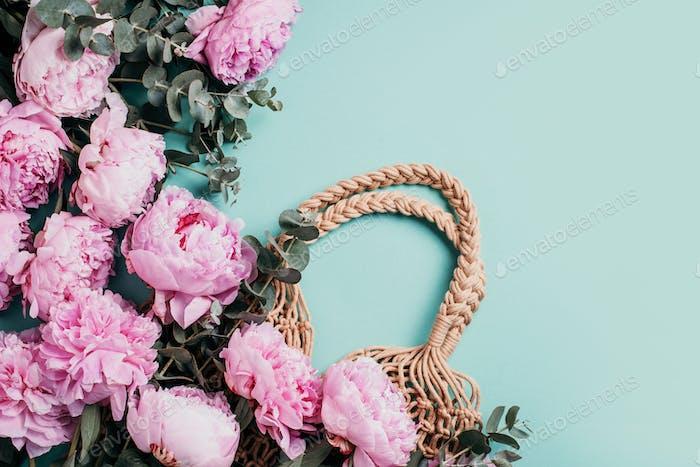Bolsa de paja con flores de peonía, flor de eucalipto sobre fondo azul. Copiar espacio. Lay plano.  Top