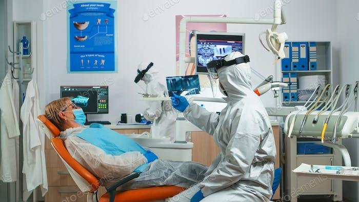 Zahnarzthelferin im persönlichen Schutzset zur Untersuchung von Zahnröntgenaufnahmen