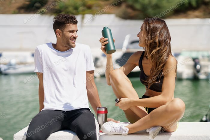 Placeit – Young sporting couple hydrate with water in metal cans while taking a break after sport