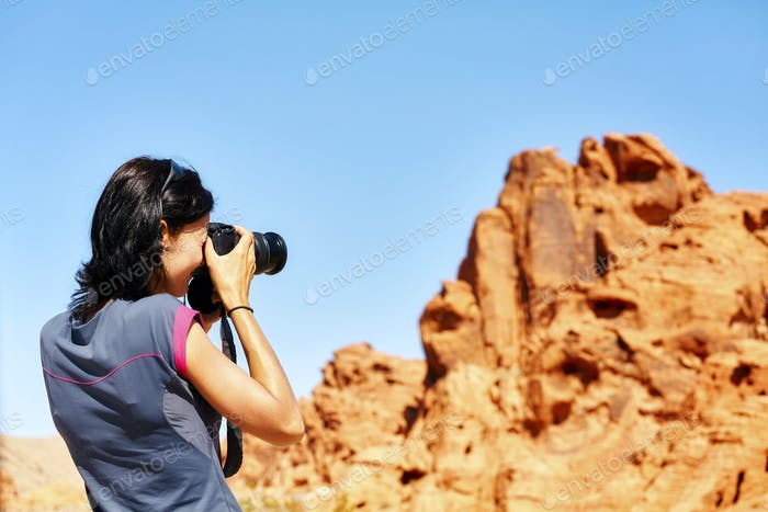 Female fit photographer takes pictures of rock formations.