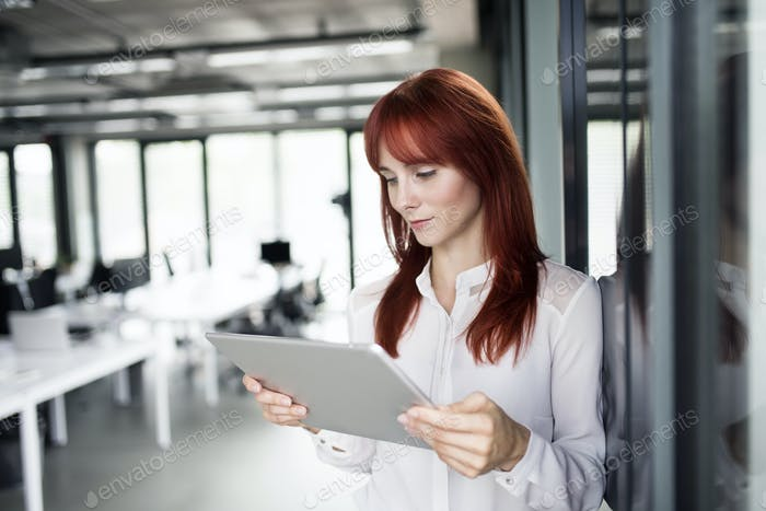 Businesswoman with tablet in her office working.