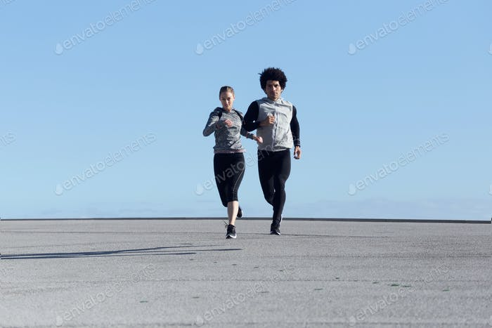 Fit and sporty couple running in the street.
