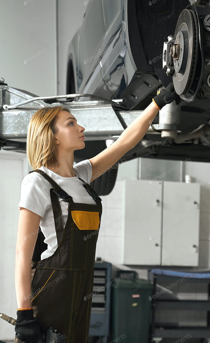 Woman looking at tire of car in auto service