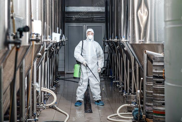 Junger Mann arbeitet in der Herstellung Fabrik in Schutzanzug und reinigt