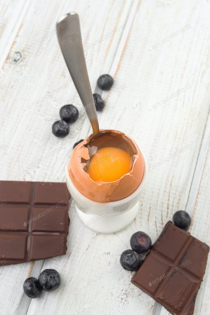 white-egg falling from an open raw egg on white wood with chocolate and blueberries, overhead shot