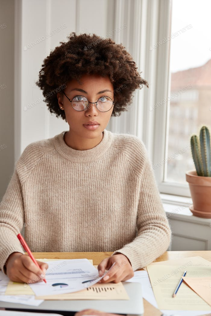 Serious attractive woman student sits in coworking space, prepares course paper in economics, studie