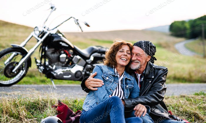 A cheerful senior couple travellers with motorbike in countryside