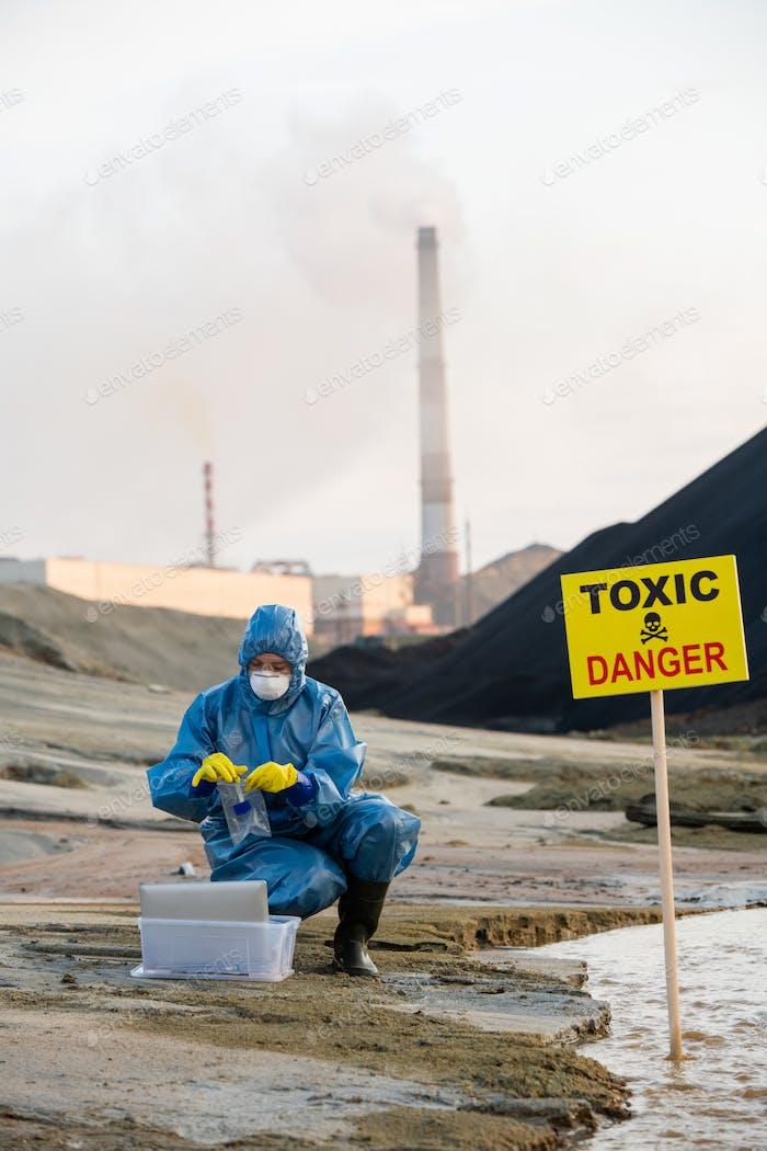 Zeitgenössische Ökologe setzen Kolben mit Probe von giftigem Boden oder Wasser in Kolben