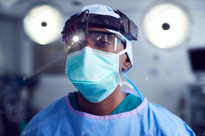 Porträt von männlichen chirurgen tragen schutzbrille und kopf licht in krankenhaus operationstheater