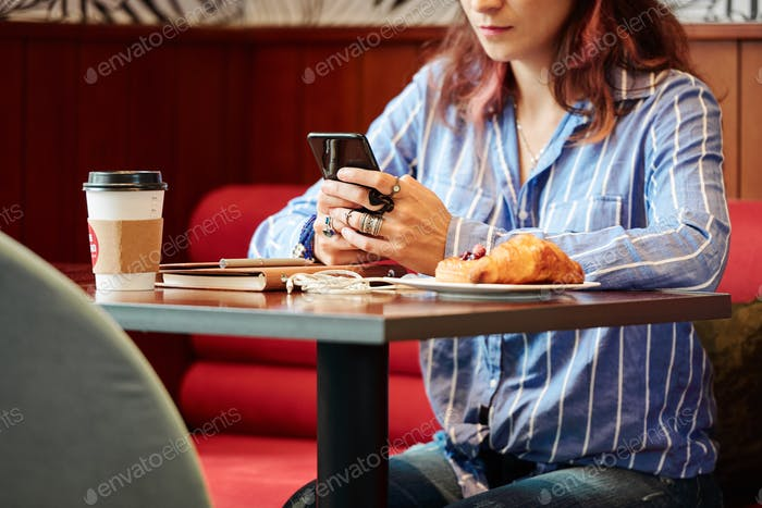 Texting woman sitting at cafe table
