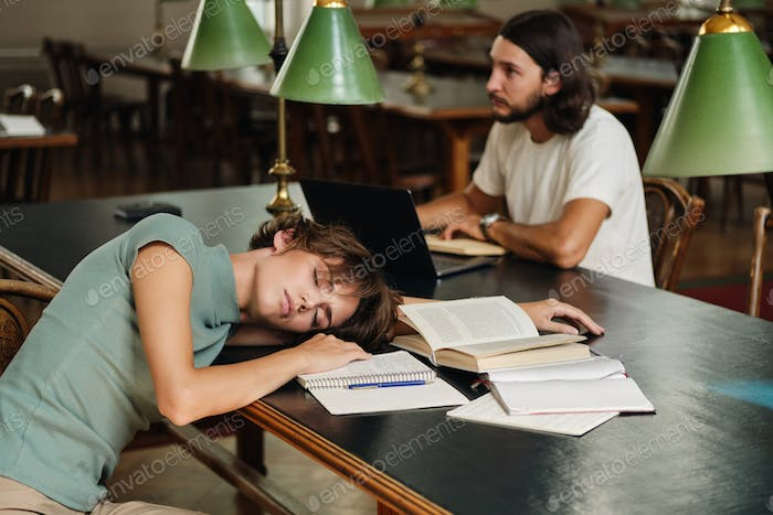 Young tired female student sleeping on desk with books during study in library of university