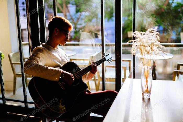 asiatischer Künstler Mann spielen Gitarre im Café