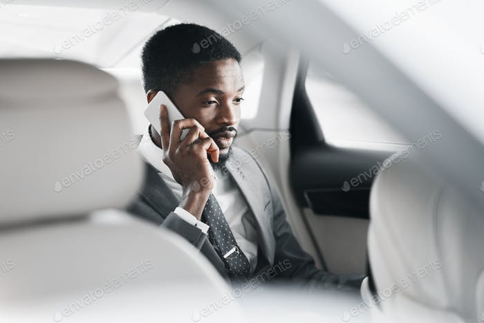 Business talk in car. Businessman talking on mobile phone