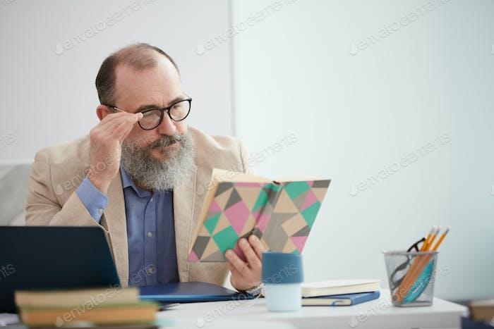 Bearded Senior Teacher at Desk