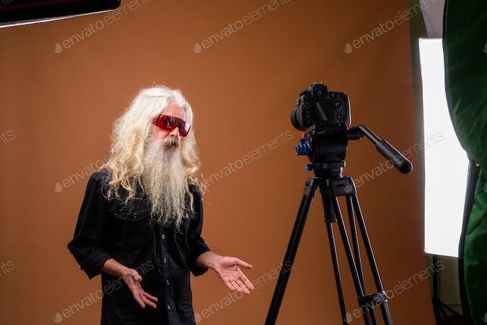 Portrait of senior bearded man vlogging in studio