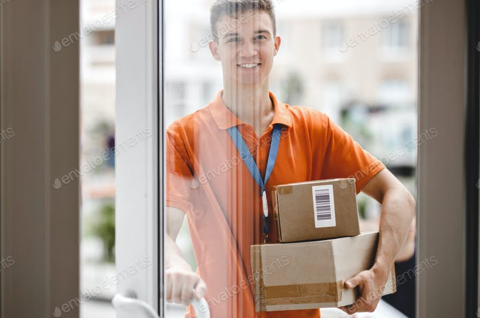 A smiling person wearing an orange T-shirt and a name tag is standing behind the glass door and