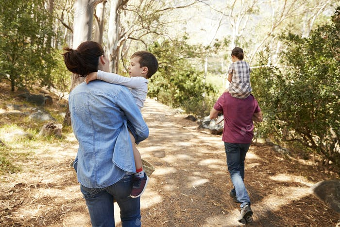 Children Riding On Parent's Shoulders On Countryside Walk