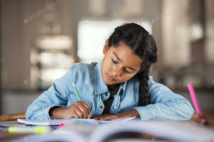 Niña india estudiando en casa
