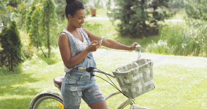 Charming woman with bicycle and phone