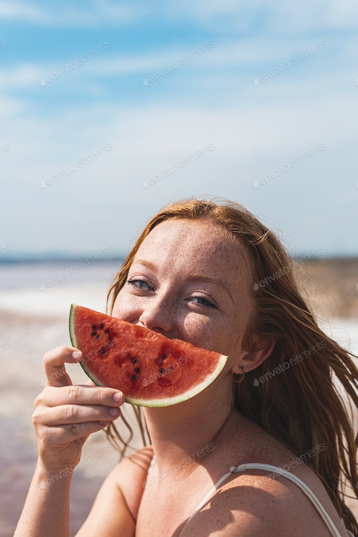 cute teenager woman covering face with watermelon smiling
