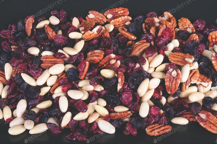 Dried fruits assortment on dark background, health food concept. Toned