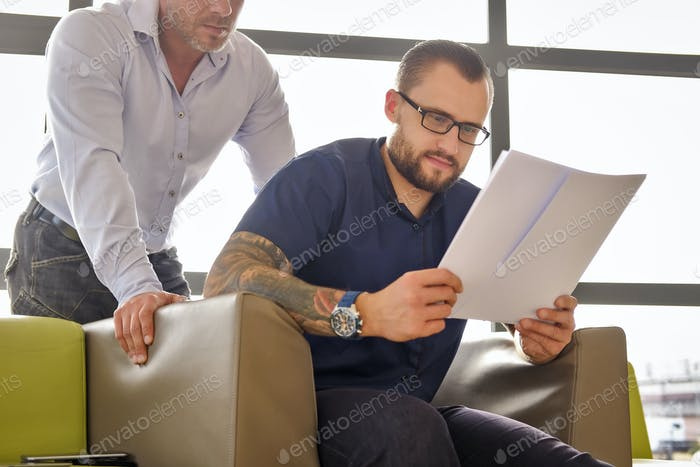 Businessman dressed in a blue shirt sitting on the couch in the office