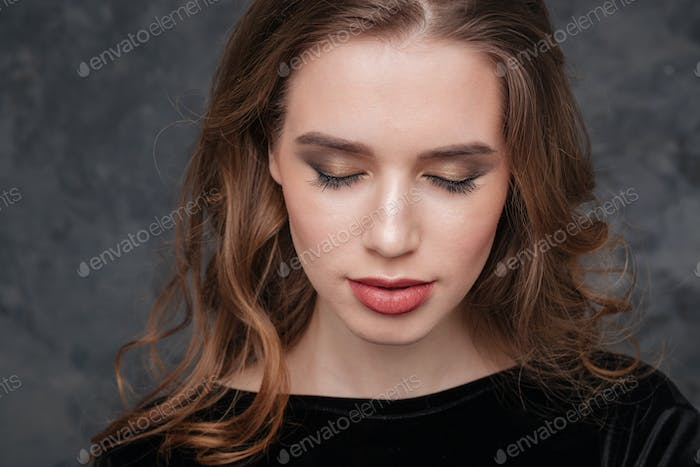 Beautiful young woman with closed eyes and modern makeup
