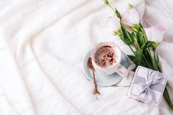 Tener una taza de café con chocolate, flores eustoma y caja de regalo en manta en la cama. Vacaciones