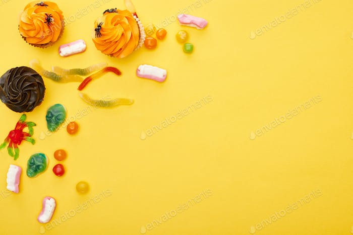 Draufsicht auf bunte Gummibüßigkeiten und Cupcakes auf gelbem Hintergrund, Halloween-Leckerbissen