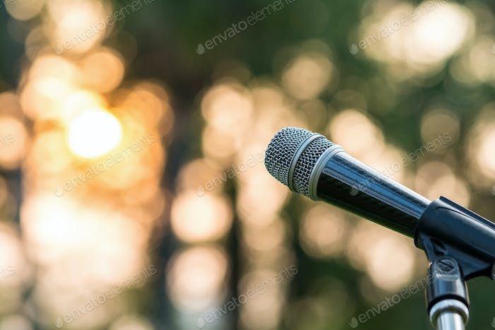 Microphone on the stage over the Abstract blurred photo of green tree with sunset light