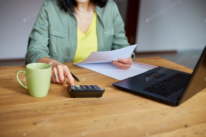 Close up of woman sit calculate expenses on calculator at wooden table