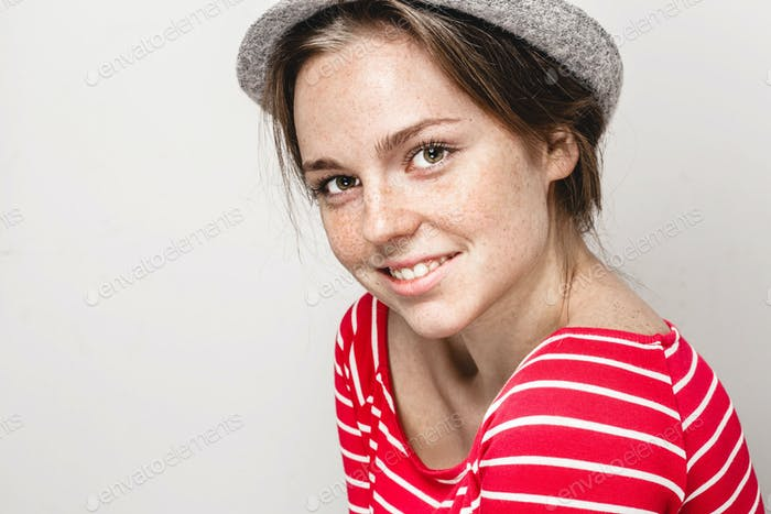 Studio portrait of a beautiful young woman with  freckles  in cap and stripes clothes