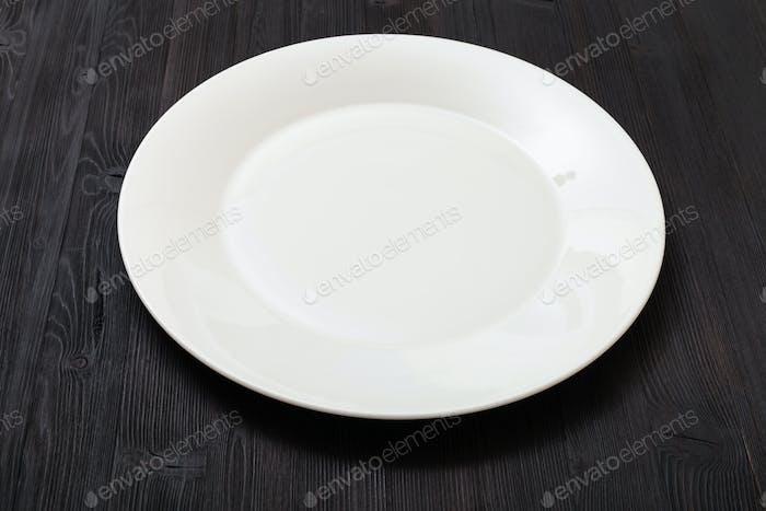 weißer Teller auf dunkelbraunem Tisch