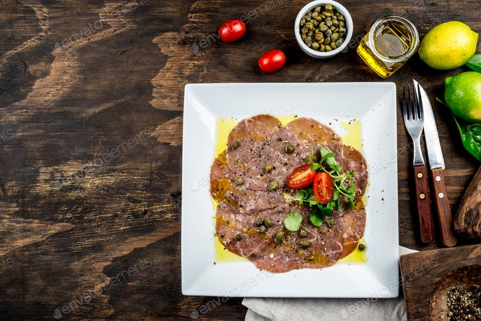 Raw BEEF CARPACCIO on white plate, wooden background, top view