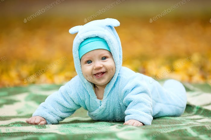 Happy baby boy in autumn park