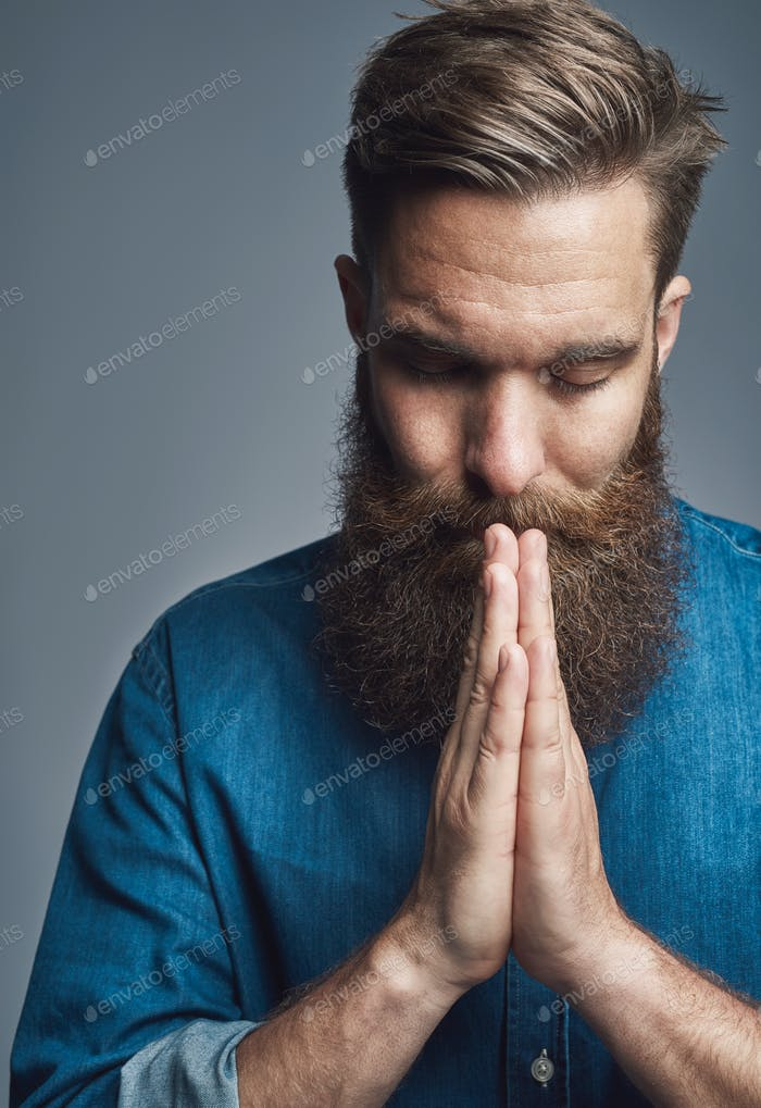 Bearded young man with hands clasped in prayer