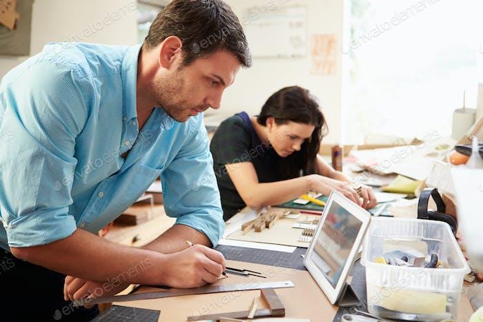Zwei Architekten machen Modelle im Büro mit digitalem Tablet