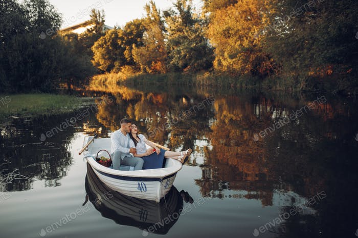 Love couple with fruit basket lying in a boat