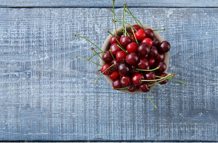 Sweet fresh cherries on blue wood background