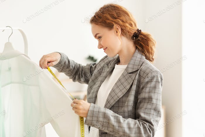 Young dressmaker measuring shirt sleeve with measuring tape